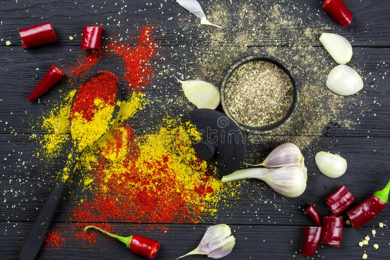 Red pepper, ground garlic in a black bowl, powder of spices and a head of garlic on a black wooden background stock images