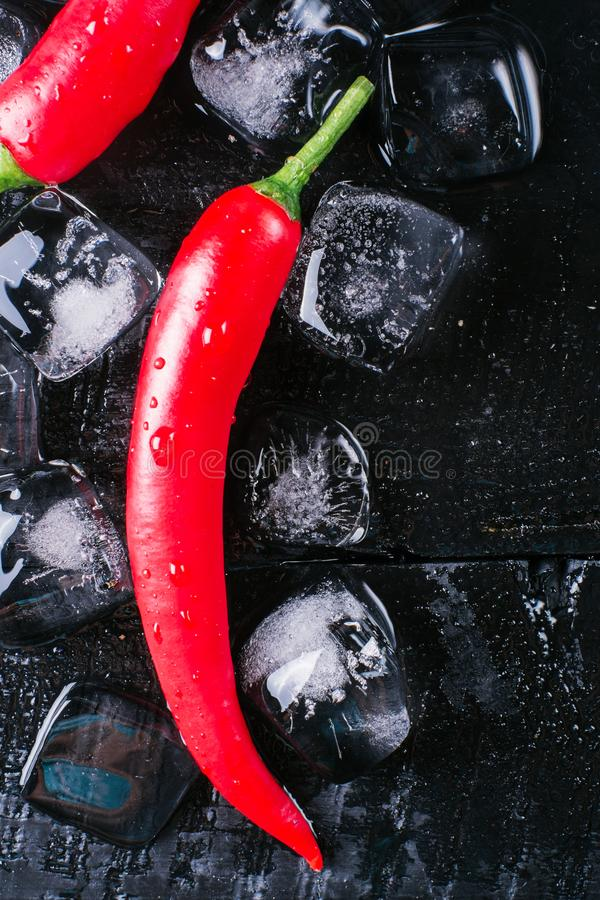 Red pepper and ice on a black wood background, fresh hot food on vintage table, freeze cold cube ice, mock up top view royalty free stock photography