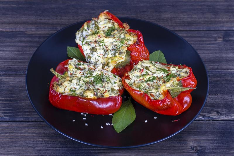 Red peppers stuffed with cream cheese with herbs and garlic, baked in grill in black plate royalty free stock photo