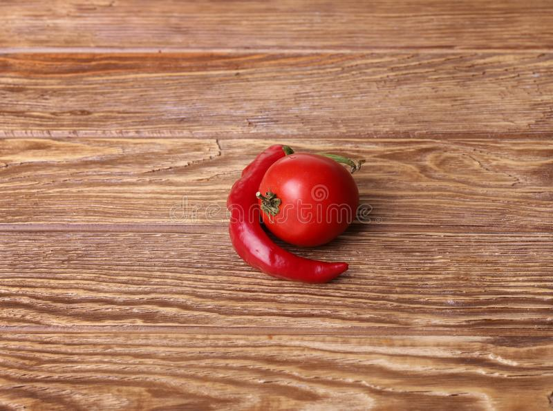 Red peppers and tomato wood grain background. Or table royalty free stock images