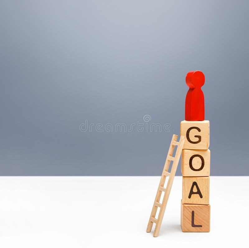 The red person climbed a tower of GOAL blocks. Developing strategy. Attracting investment and financial resources for a successful royalty free stock photography