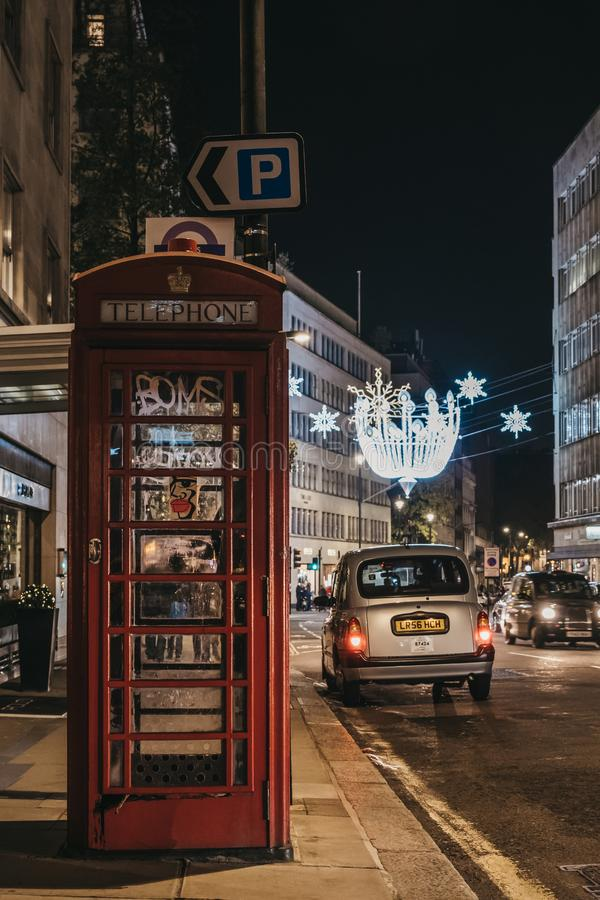 Red phone box on Bond Street, London, UK, city street on the background. London, UK - November 17, 2019: Red phone box on Bond Street, London, street on the royalty free stock images