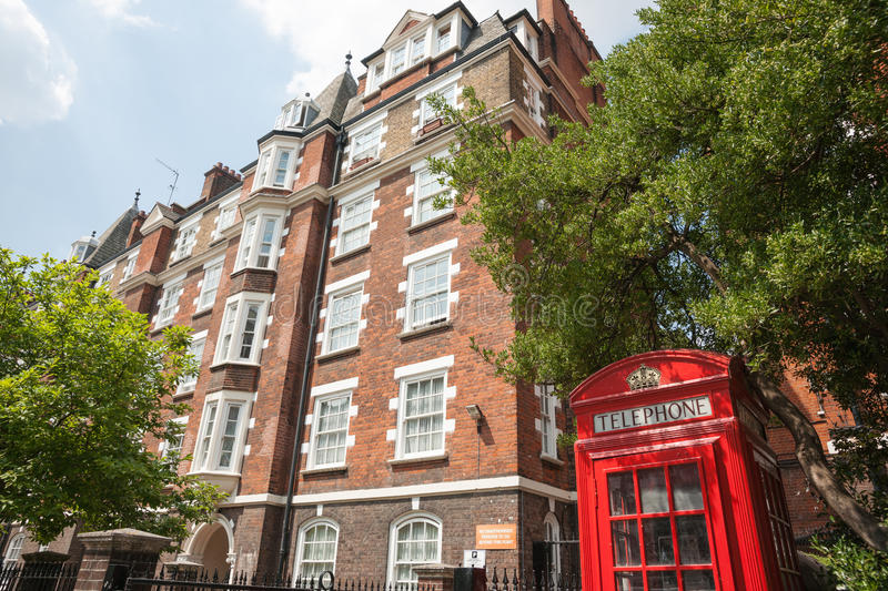 Red Phone Box In Front Of Red Brick Apartments. Stock Image ...