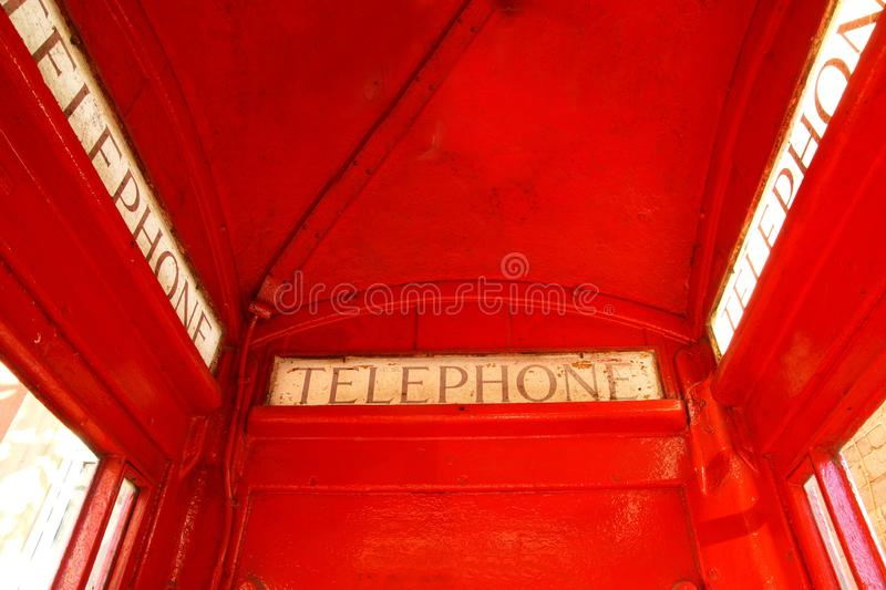 Close up of Classic English London Phone Booth, Red cabin with windows. The word Telephone is written on the red phone box. A red phone box, view of the Classic stock photo