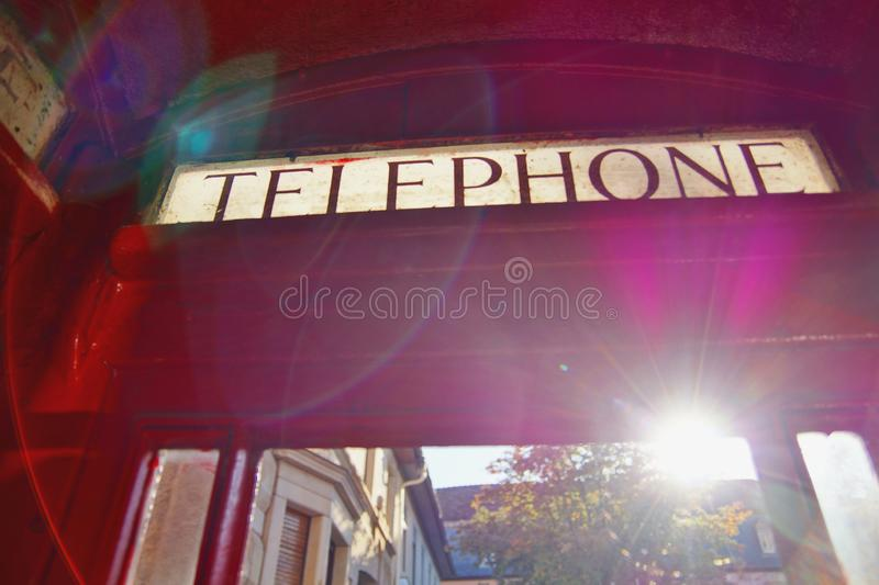 Close up of Classic English London Phone Booth, Red cabin with windows. The word Telephone is written on the red phone box. A red phone box, view of the Classic stock photography