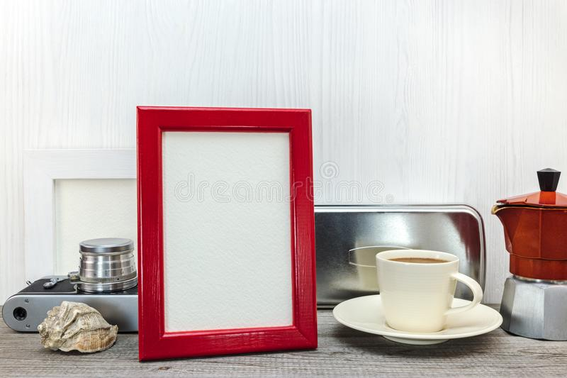 red photo frame and coffee pot with cup on white wooden background stock photo