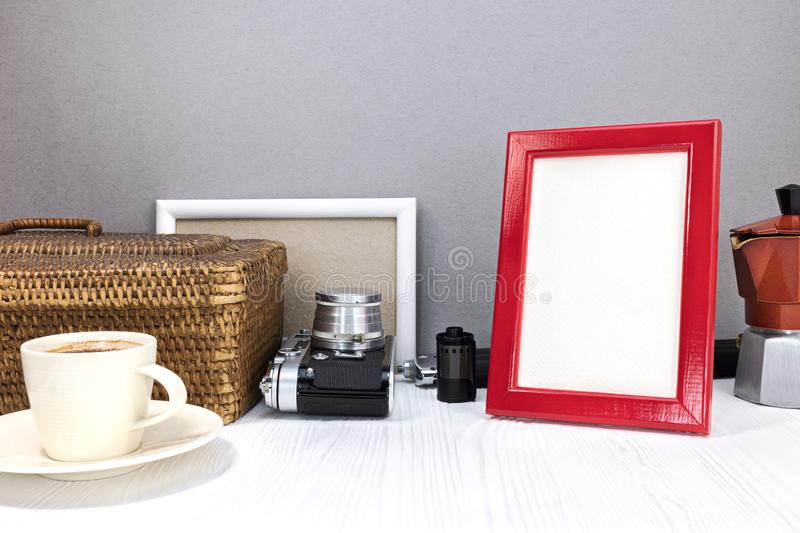 Red photo frame, retro camera and coffee pot with cup of coffee stock images