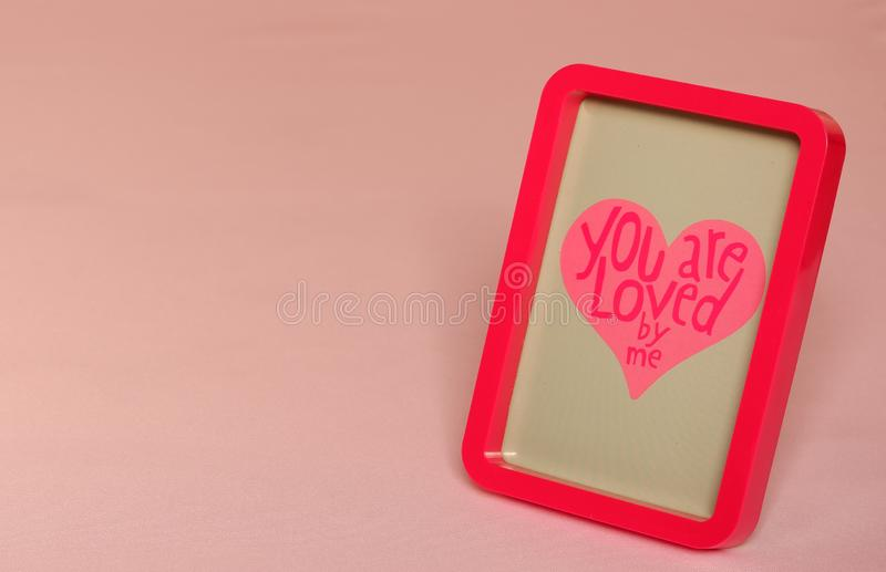 Red photo frame with text in pink letters background. Red photo frame with text in pink heart blue grey background beautiful wedding valentine decoration romance royalty free stock image
