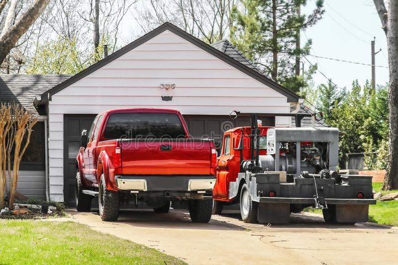 Red pickup truck and older red truck with welder on the back parked in the driveway in front of a residential garage and house stock photography