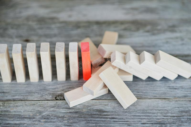 Red piece of domino resisting to domino effect, stopping the falling o the line royalty free stock photography