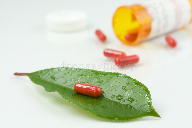 Red pill over a green leaf royalty free stock images