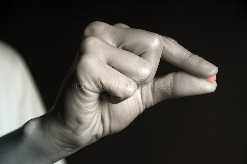 Red Pill - Pill between Fingers. Red generic pill between female fingers royalty free stock photo
