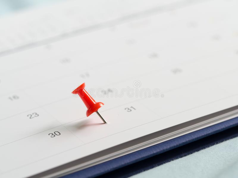 Red pin push on day 31 of end month on white calendar. Mark this day as salary date. Concept of meeting appointment reminder.  stock images