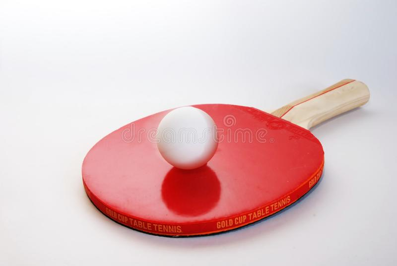 Red ping-pong paddle with the ball stock image