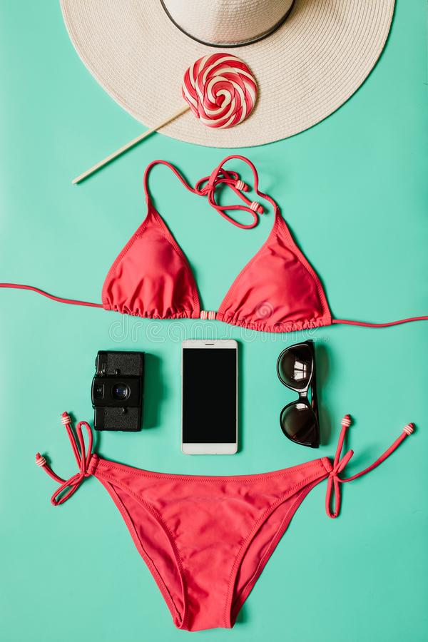 Red, pink bikini suit, lollipop, sunglasses, smartphone, film camera, hat on plain light cyan background. Summer vacation concept stock photo