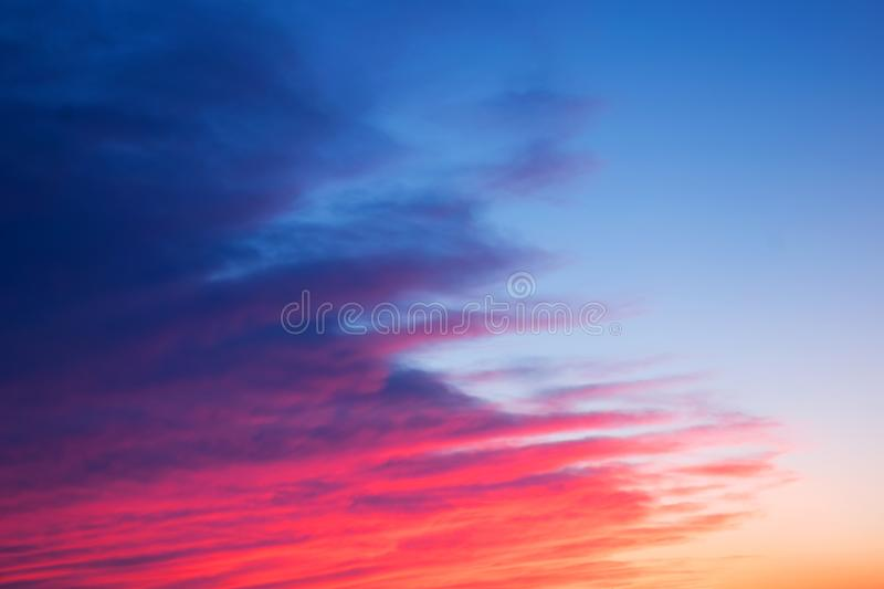 Red, pink and blue bright sunset with beautiful diagonal clouds. royalty free stock photos