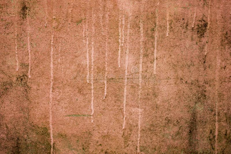 A red pink dirty old concrete wall with light spots and stripes of paint. mold and moss on the surface of the wall. rough texture royalty free stock photos