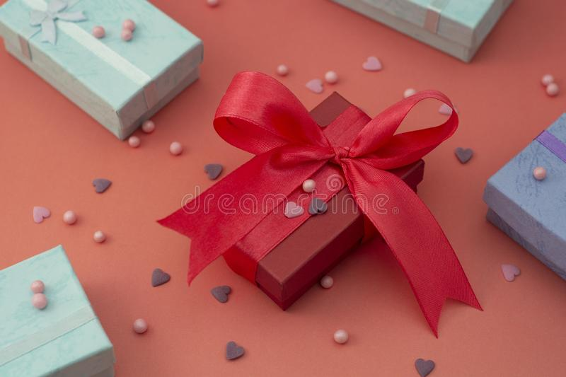 Red, pink gift box with big bow, on colorful red or pink board. Top view with copy space. Birthday, surprise gift box. Big bow royalty free stock images