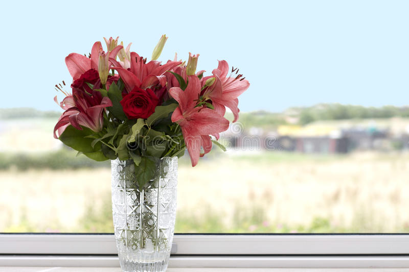 Red and pink lilies in a crystal vase stock photography