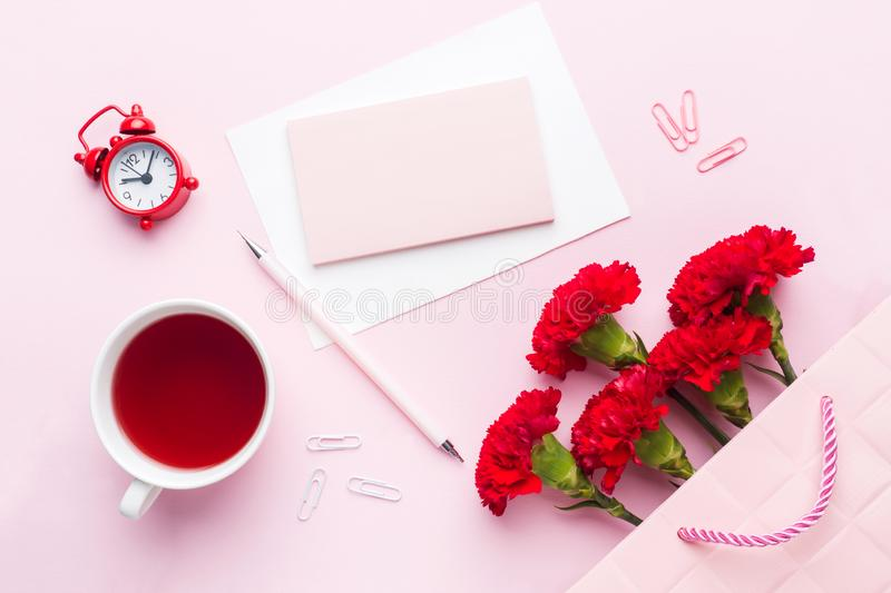 Red-pink objects. Cup of tea, carnation flowers Notepad for text on pastel pink background. Copy space. Top view Flat lay royalty free stock image