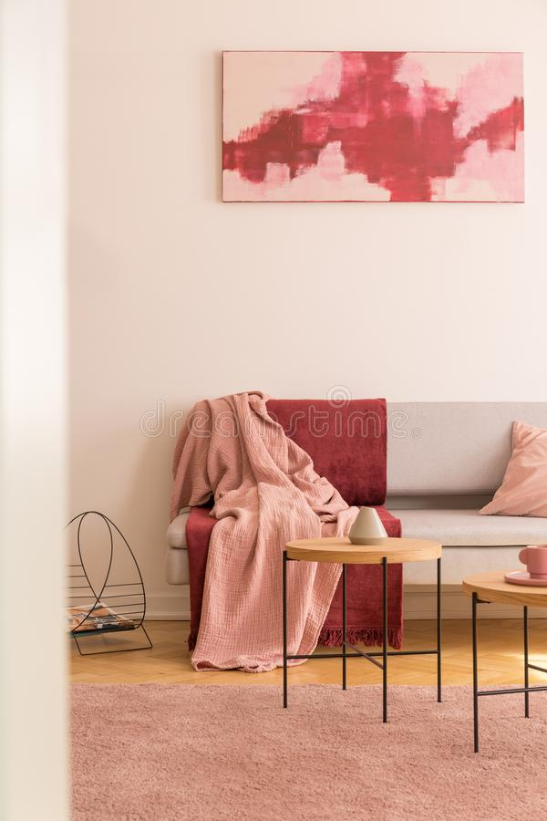 Red and pink poster above grey couch with blankets in living room interior with carpet. Real photo. Concept photo stock photos