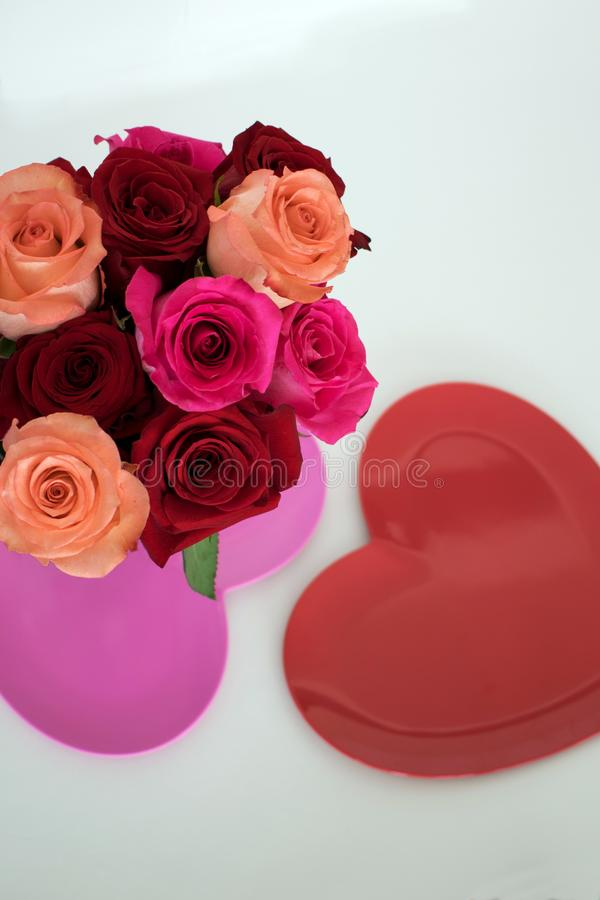 Red and pink roses arranged on top of pink heart shaped plate stock image