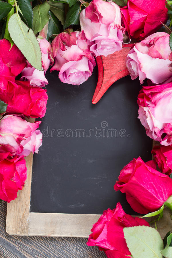 Red and pink roses frame on table. Frame of blooming dark and pink roses with heart laying on black table royalty free stock images