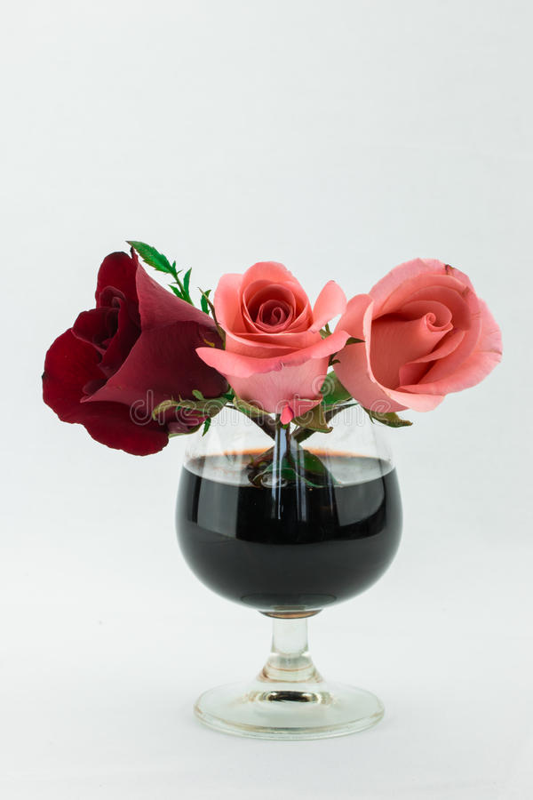 Red and pink roses in glass of wine. Red rose and pink roses in glass of wine stock image
