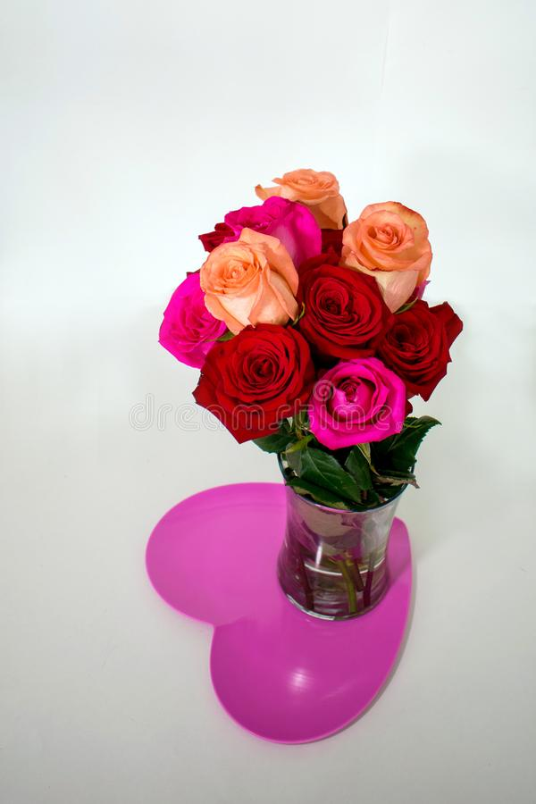 Red and pink roses in vase on top of pink heart stock photography
