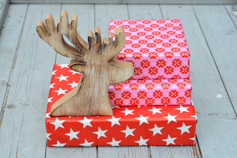 Red and pink star flower pattern christmas gifts with wooden reindeerwith on a wooden shelves background. Red and pink star flower pattern christmas gifts with stock images
