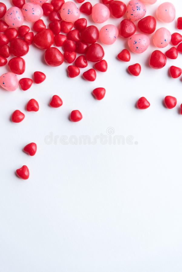 Red and pink Valentine`s Day cinnamon hearts and jellybeans with white background royalty free stock images