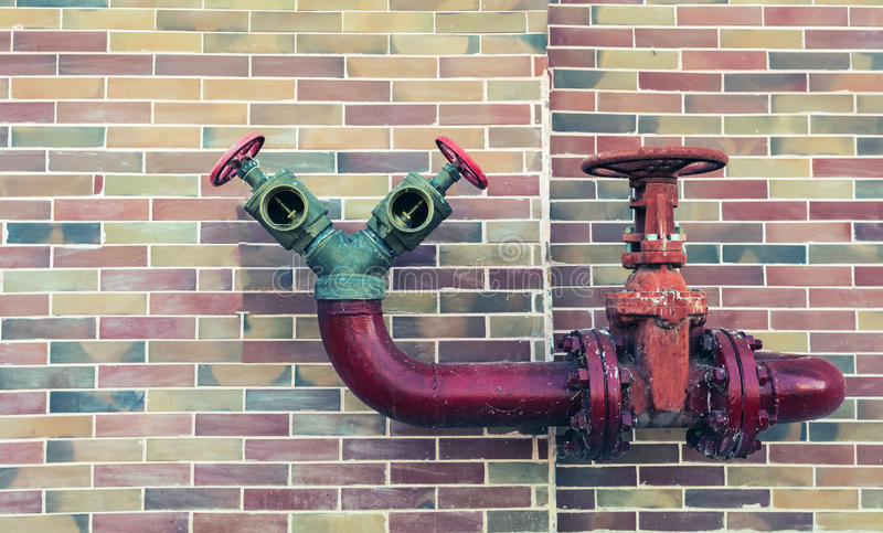 Red pipe line with brown valve on colorful brick wall royalty free stock images