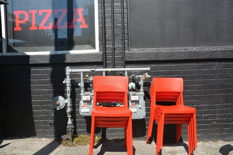 Red pizza sign and orange chairs in Portland, Oregon. This is a red pizza sign with orange chairs against a black wall in downtown Portland, Oregon royalty free stock photos