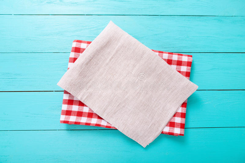 Red plaid tablecloth and gray one on blue wooden table. Top view and copy space royalty free stock photos
