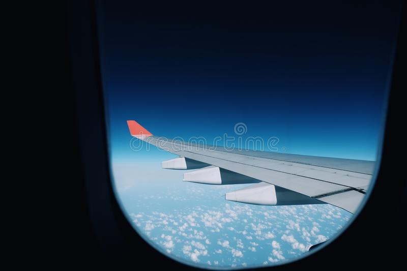 Red plane wings and blue skies,view from airplane window. Sky, flight, fly, aircraft, transportation, aviation, travel, background, jet, cloud, white, high stock images