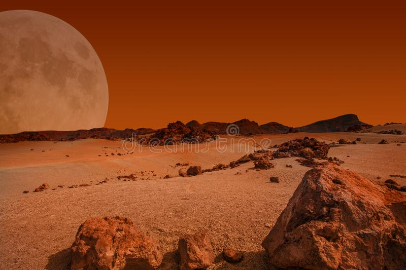 Red planet with arid landscape, rocky hills and mountains. And a giant Mars-like moon at the horizon, for space exploration and science fiction backgrounds royalty free stock photos