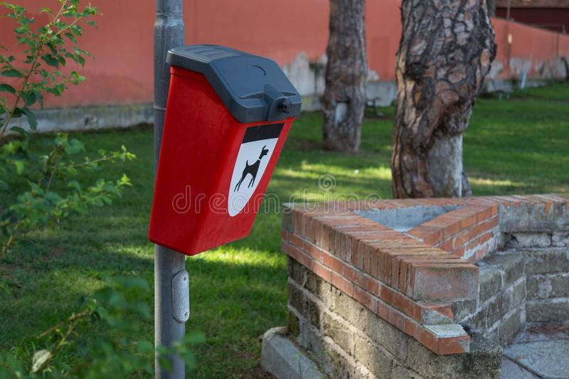 Red plastic bin for dog poo in the park. Image of dog on the container. Concept of clean environment royalty free stock image