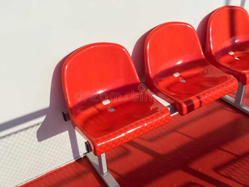 Red plastic chairs in front of a white wall.  royalty free stock photography