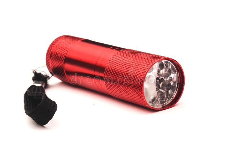 Red plastic flashlight isolated on white background. Small, bulb, equipment, lamp, tool, torch, electric, object, bright, electricity, glass, handle royalty free stock photos