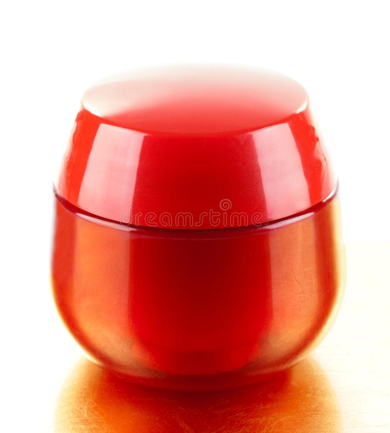 Red plastic jar with cosmetic cream royalty free stock images