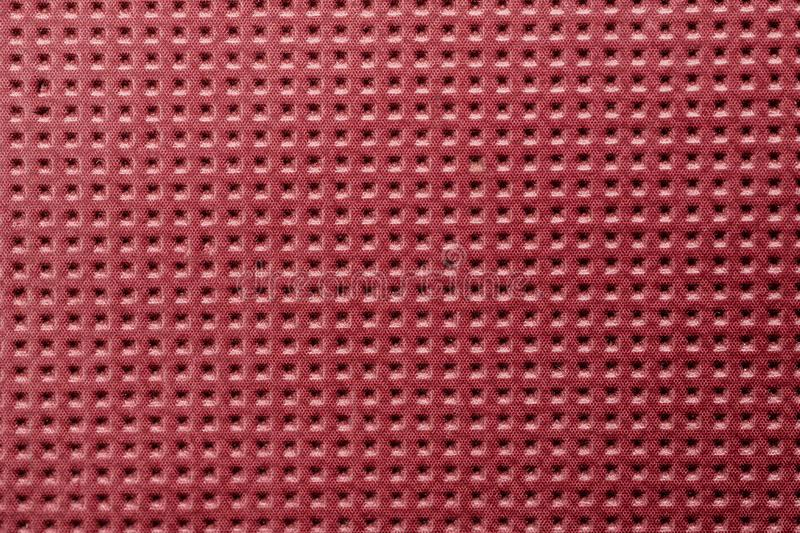 Red plastic material with symmetric square holes, abstract texture. Background, metal, pattern, design, wallpaper, backdrop, gray, textured, grill, seamless royalty free stock photos