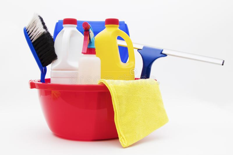 Plastic pail with cleaning supplies. A red plastic pail with cleaning supplies, detergents, squeegee, rag, brush royalty free stock photography