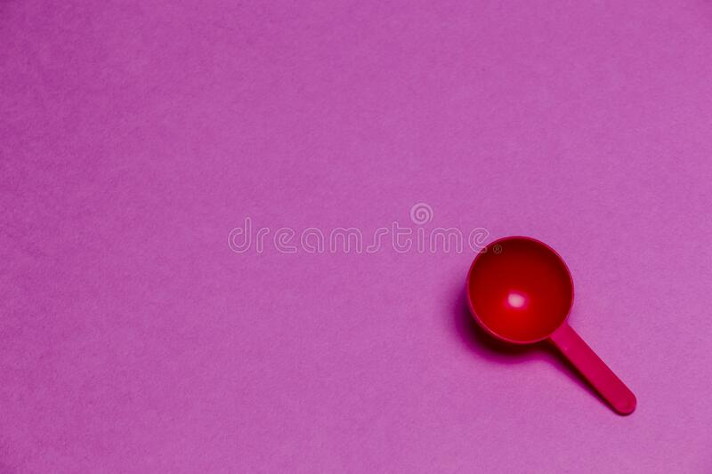Red Plastic Round Spoon Placed Over Colorful Pink Background royalty free stock photography