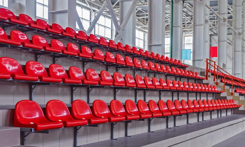 Red plastic seats in the stadium. Tribune fans. Seats for spectators in the stadium.  royalty free stock images