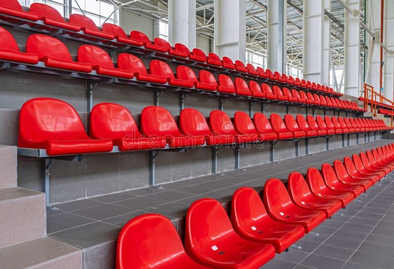 Red plastic seats in the stadium. Tribune fans. Seats for spectators in the stadium.  stock image