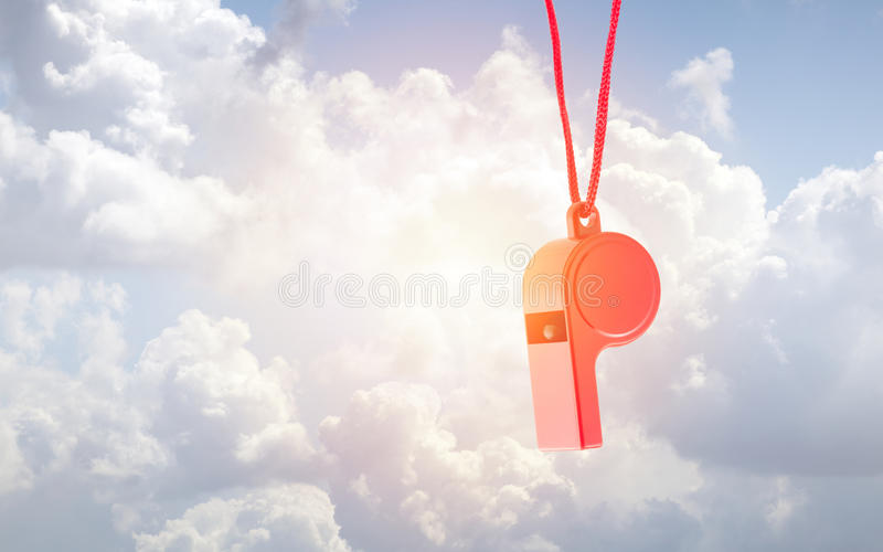 Red plastic whistle over sunny blue sky stock image