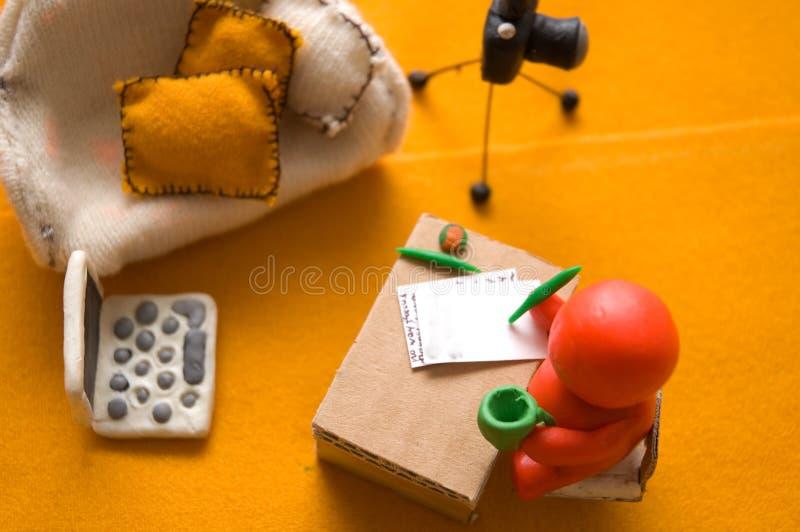 Red plasticine man. Plasticine photographer write a letter royalty free stock photos