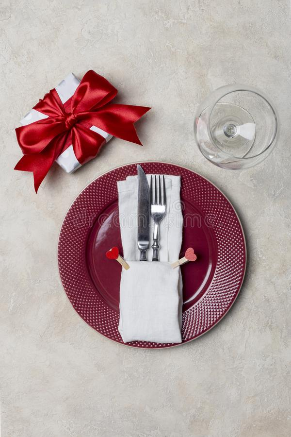 Red plate with gift box, with fork, knife and white napkin at white background stock photos