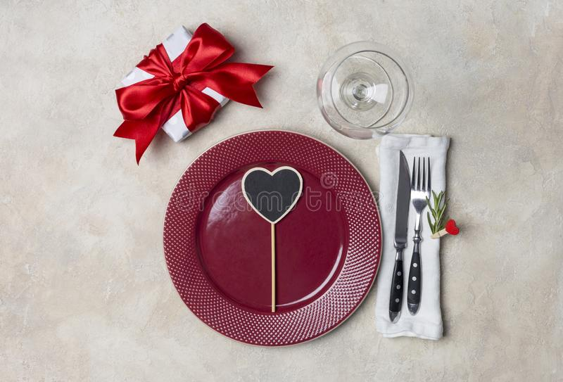 Red plate with gift box, with fork, knife and white napkin at white background royalty free stock photo