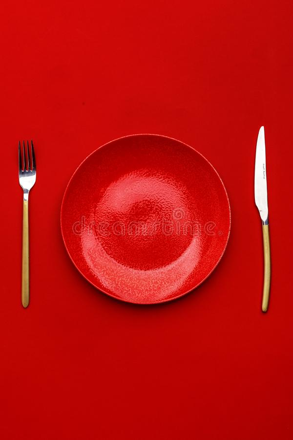 Red plate, knife and fork on a red table. Top view. Copy space royalty free stock images